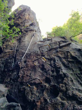 Steile Felswand mit künstlichen Eisentritten und Stahlseil