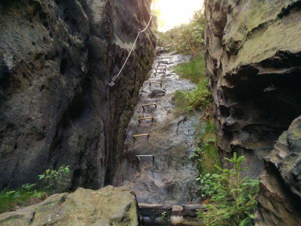 Künstliche Klettertritte mit Stahlseil an schräger Felswand