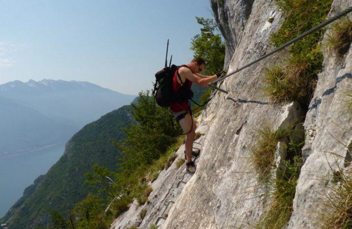 Kletterer auf einer Querung an Felswand mit Eisentritten