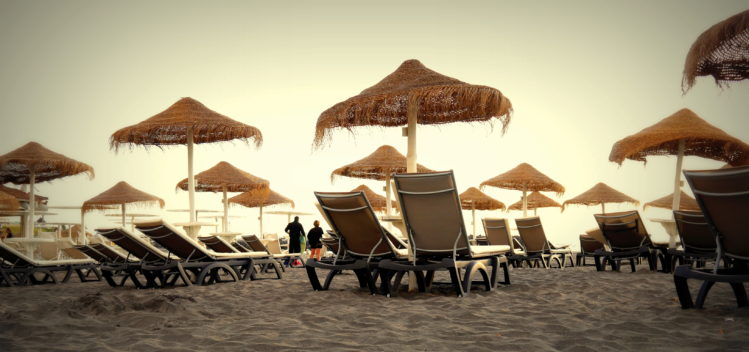 Liegestühle und Sonnenschirme am Sandstrand