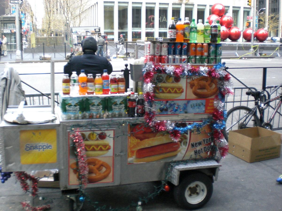 Ein Straßenverkäufer steht dick eingepackt hinter seinem bunt mit Lametta dekorierten Stand.