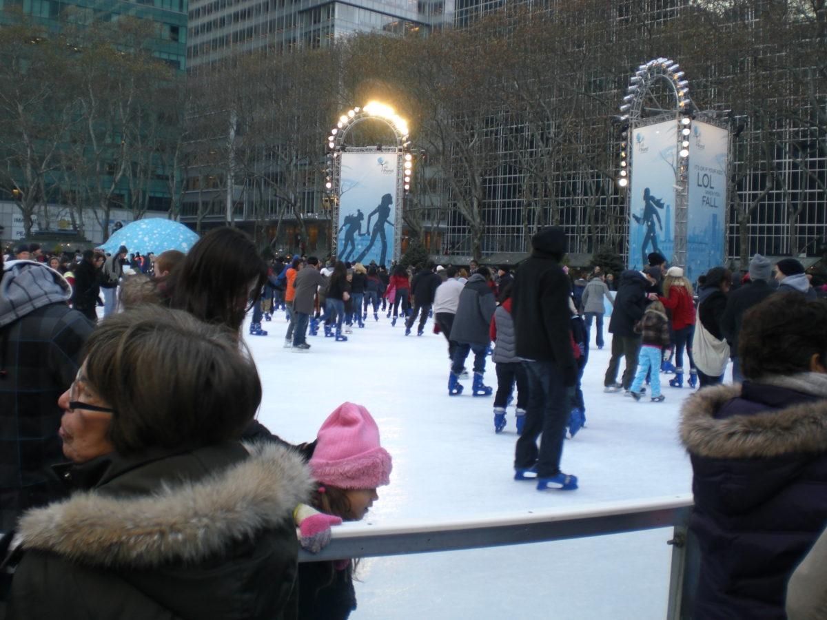 Auf einer Eisfläche im Bryant Park tummeln sich viele Eisläufer.