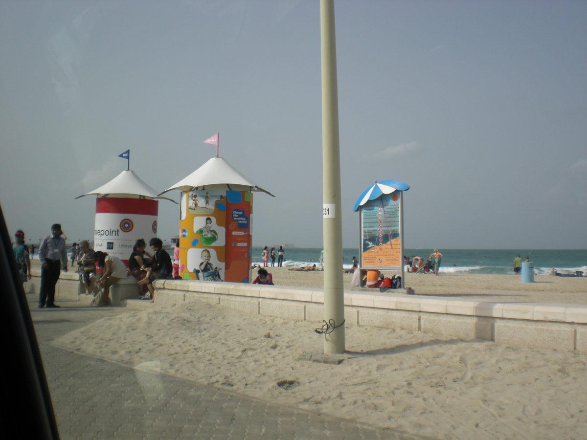 Zwei Umkleiden am Strand in Dubai: Die eine mit einer rosa Fahne auf dem Dach, die andere mit einer blauen.