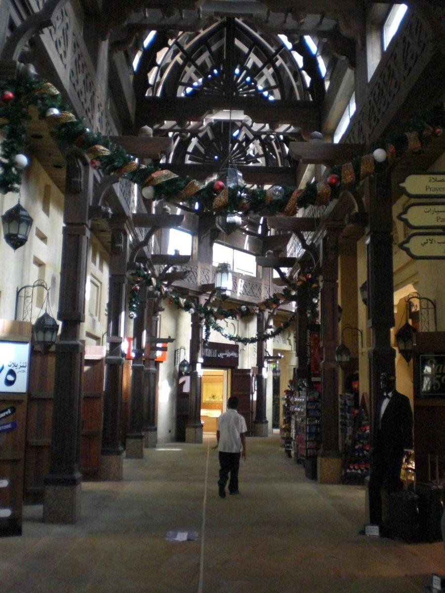 Von der Decke eines überdachten Basars hängt Weihnachtsschmuck.