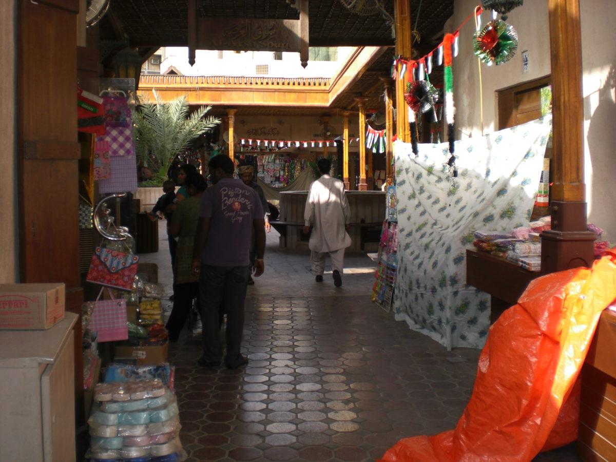 Souk - hier bekommt man so ziemlich alles und vor allem viel Touristen-Neppes. Die Farben der Vereinigten Arabischen Emirate - Rot, Weiß, Grün, Schwarz - sind ebenso allgegewärtig wie die Portraits der Herrscherfamilie.