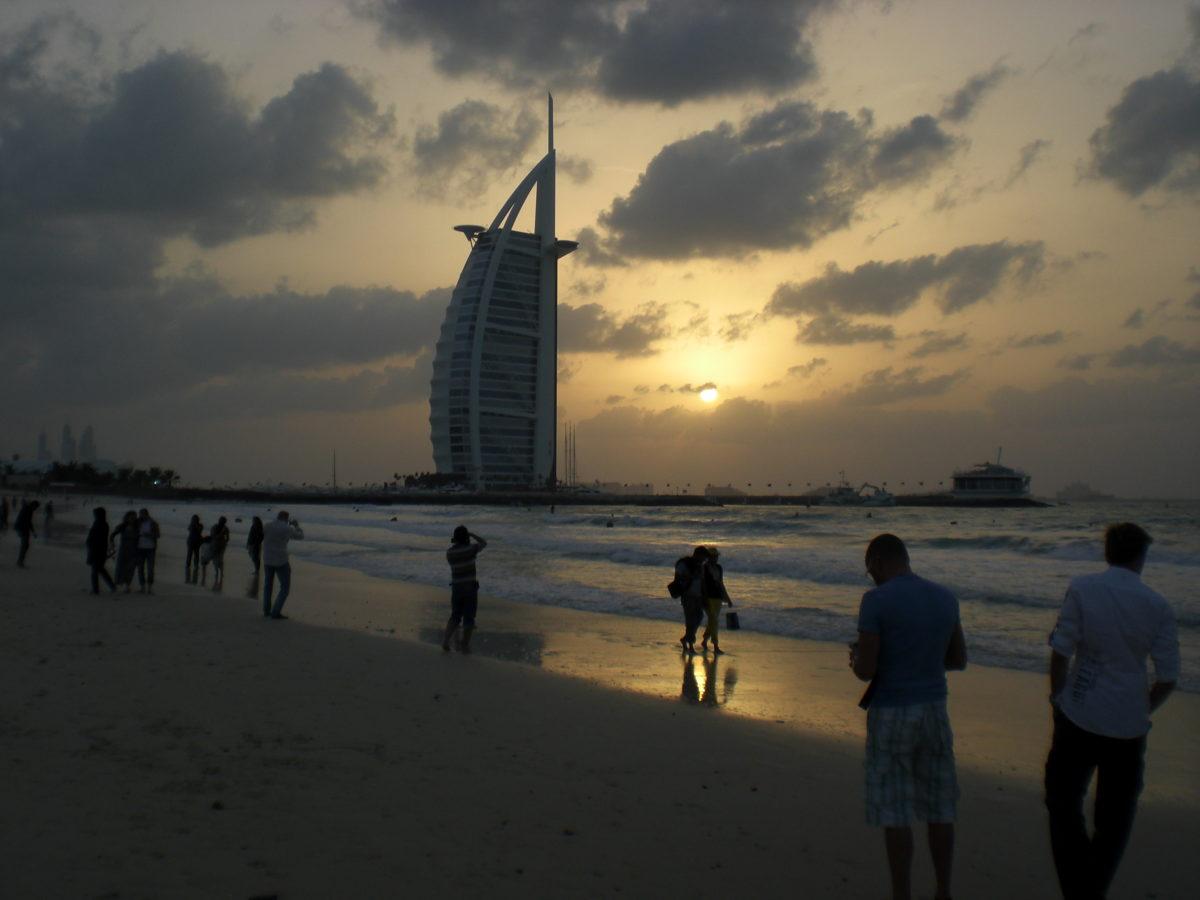 Am Strand stehen viele Touristen und machen Fotos vom Burj al Arab.