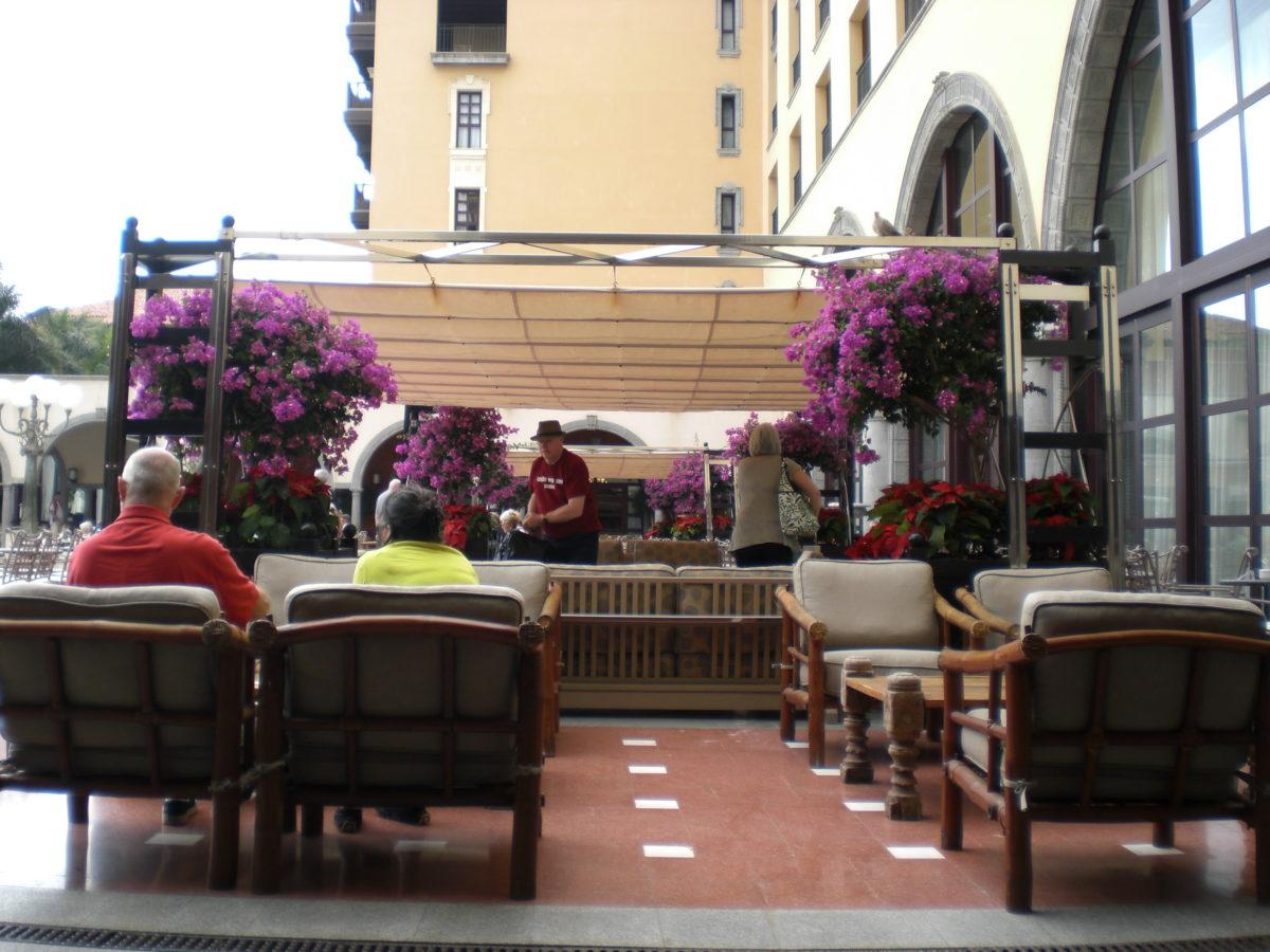 Einige Gäste des Hotels sitzen auf urigen Holzsesseln mit großzügigen Polstern. Im Hintergrund blühen bunte Blumen.