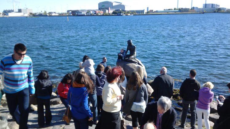eine Gruppe Touristen schaart sich um eine Figur.