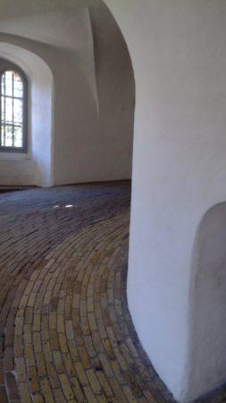 weiß gekalkte Wände umgeben einen gepflasterten Weg im Turm