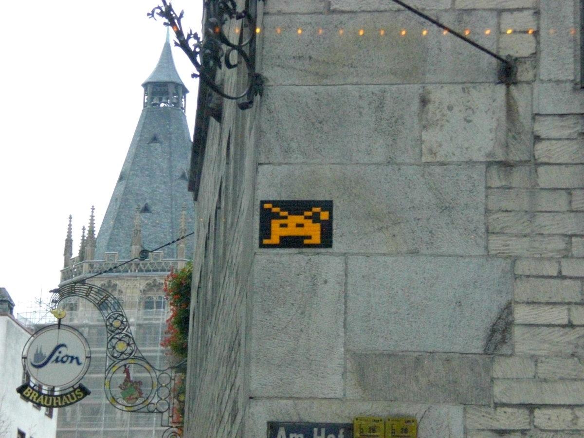 eine Straßenecke in Köln mit Straßenkunst und einem Sion-Kölsch-Schild.