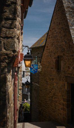 Gasse mit Lampe und Handwerkerschild in Le Mont-Saint-Michel