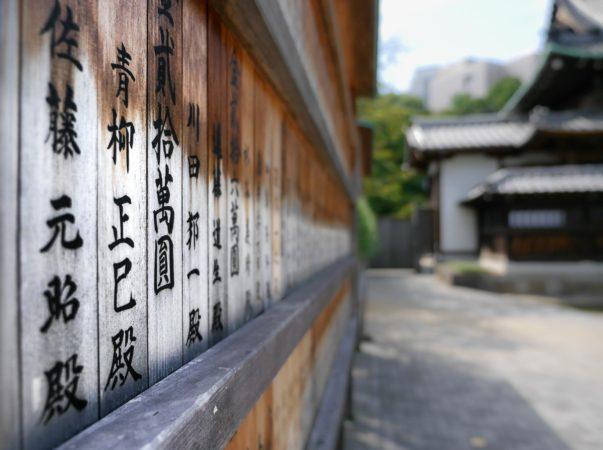 Tafel mit japanischen Schriftzeichen beim Sengakuji Tempel