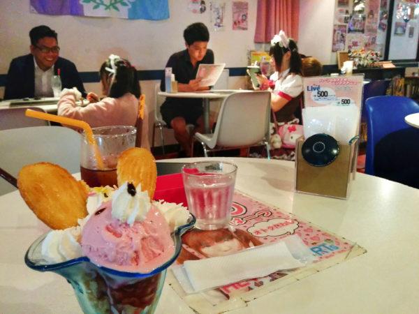 Hockende Maids zur Bedienung an einem Tisch in einem Maidcafe