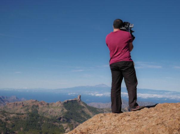 Mann mit Kamera auf Schulter auf einem Felsen
