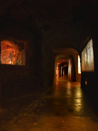 dunkler Tunnel im Museum mit beleuchteten Ausstellungskammern