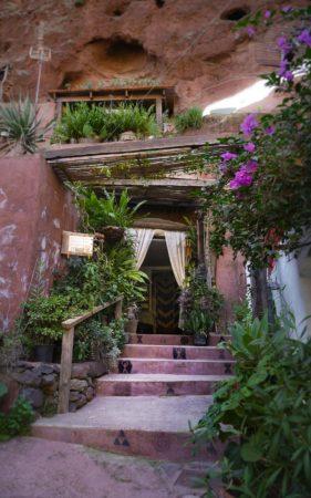 Eingangstür mit weißen Vorhang und Blumen an einer Treppe von einer Wohnung in einem Felsen