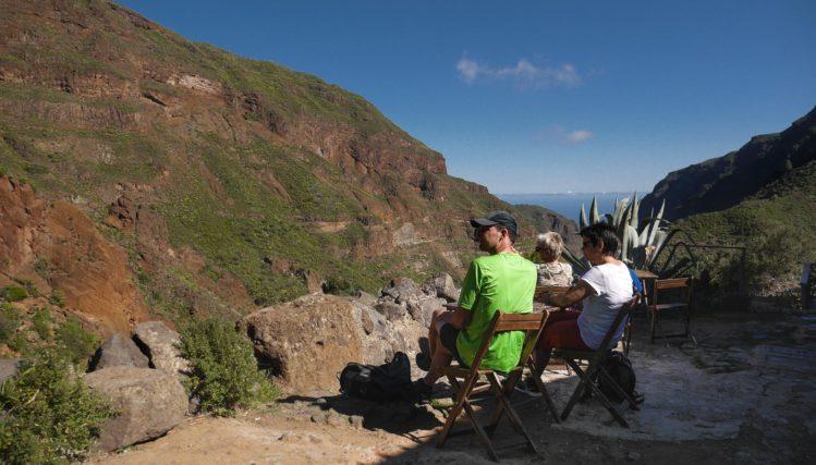 sitzende Menschen auf Holzstühlen die in einen Barranco blicken
