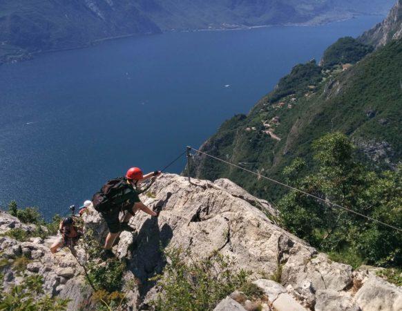 Bergsteiger an einem Klettersteig mit Gardasee im Hintergrund