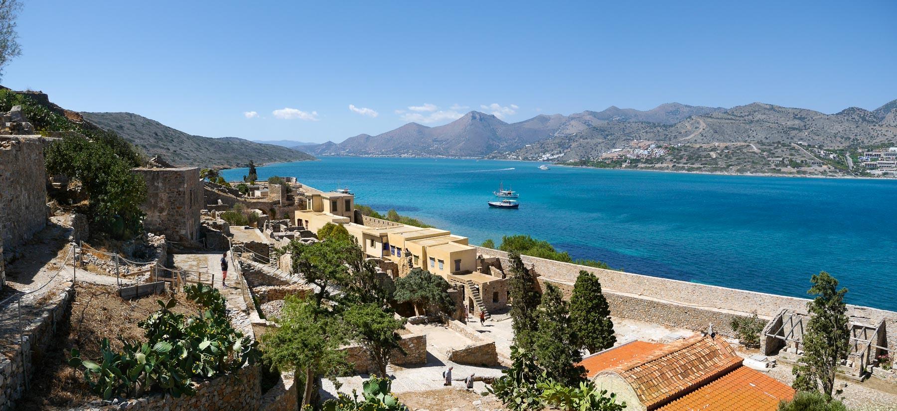 Panoramablick auf Leprasiedlung von Spinalonga mit blauem Meer und Bergen im Hintergrund