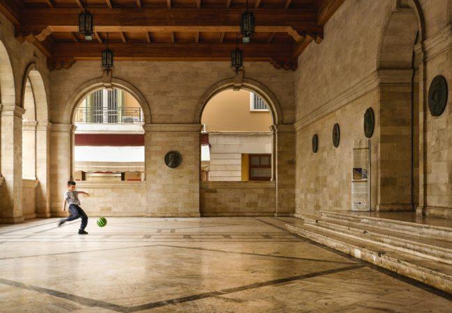 Fußball spielender Junge in der venezianischen Loggia