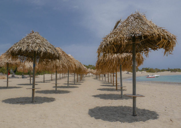 Sonnenschirme mit Palmenstroh bedeckt am Strand