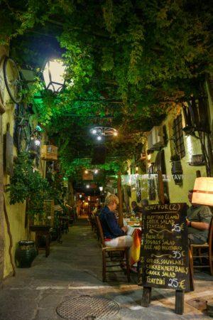 Gasse am Abend mit Weinreben und Restaurant
