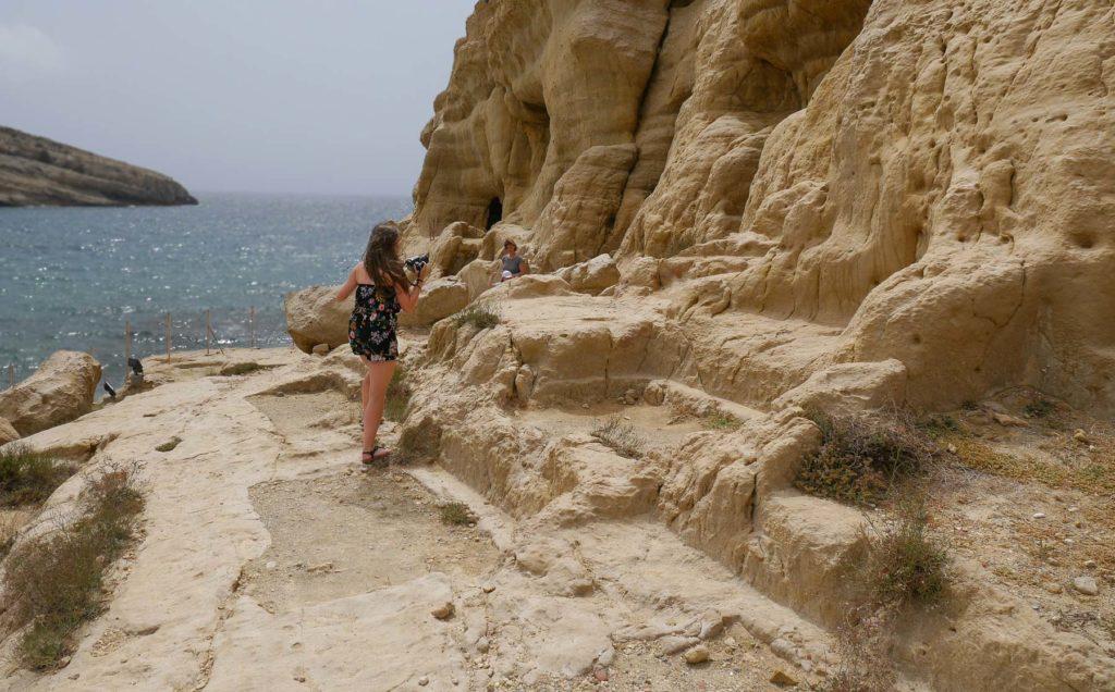 Frau auf Weg an Felswand
