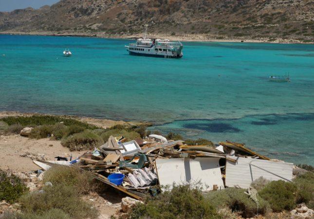 Fähre in türkisblauem Wasser und zerstörte Holzhütte am Strand