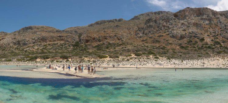 Menschen am Sandstrand vor türkisfarbenen Wasser