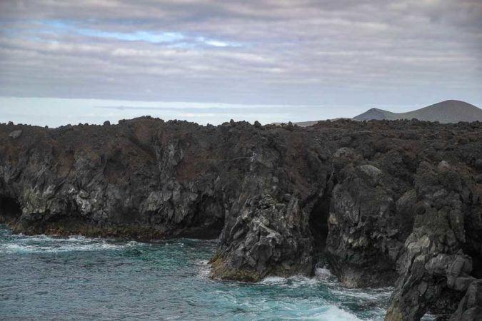 Angler im Felsen an der Los Hervideros Küstenlandschaft auf Lanzarote