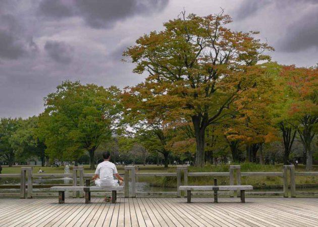 Meditierender Mann auf einer Bank