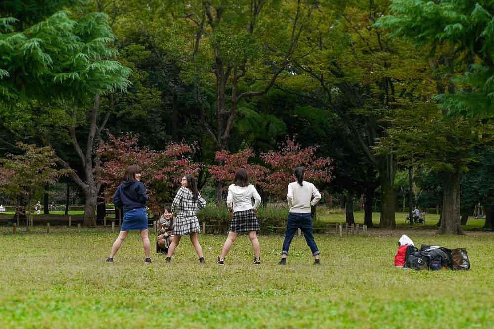 4 tanzende Mädchen auf Rasen im Yoyogi Park