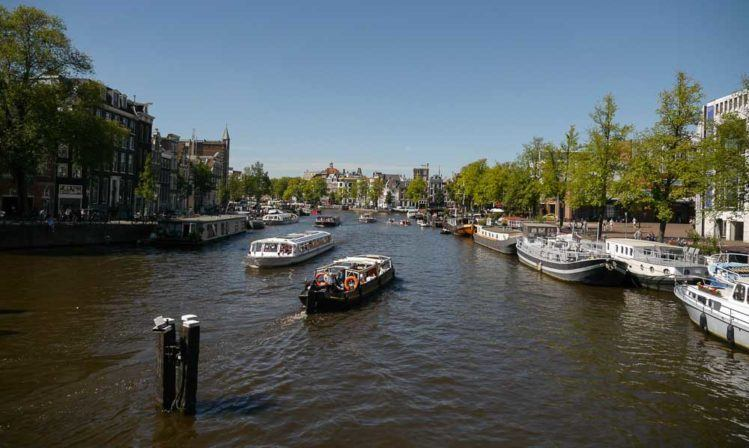 Gracht in Amsterdam mit Ausflusgboot