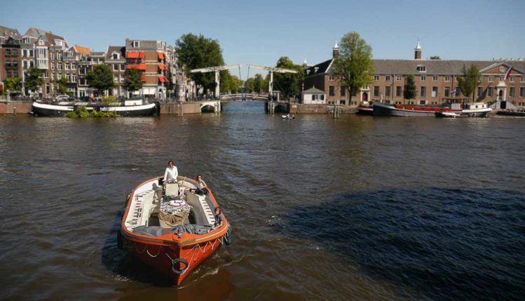 Kleines Motorboot auf Gracht in Amsterdam
