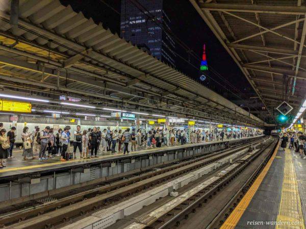 Bahnsteig in der Ausschilderung in der Shinjuku Station mit Docomo Tower