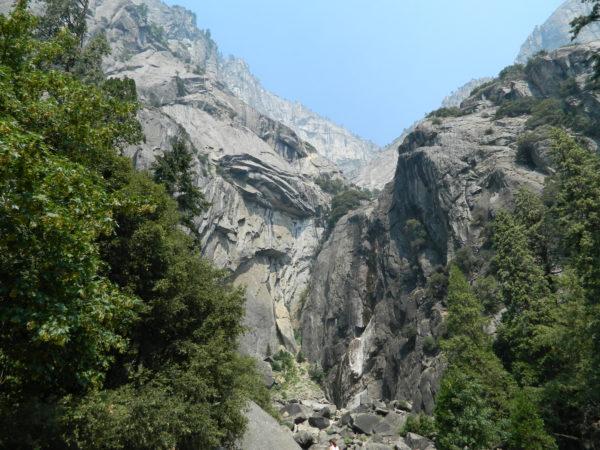 Ein Steinbruch der Granitfelsen ist von grünen Bäumen umrahmt