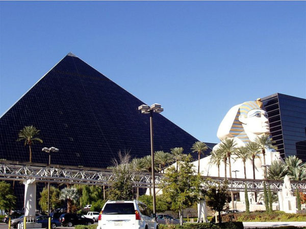 Vor der im Sonnenlicht schwarz erscheinenden Pyramide des Luxor Hotels steht eine Nachbildung der Sphinx