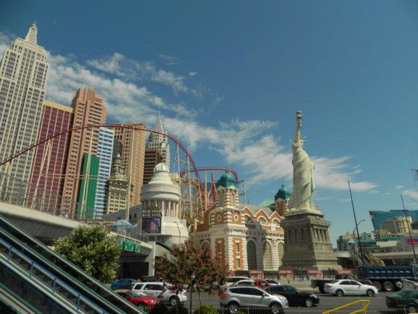 Vor dem New York New York thront die Freiheitsstatue. Im Hintergrund liegt die Miniatur-Skyline, zwischen der eine Achterbahn durchfährt