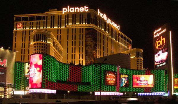 Das Planet Hollywood Hotel leuchtet in der Nacht hinter einer großen Reklametafel