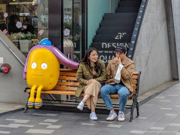 Parkbank mit Figur und jungem koreanischen Pärchen