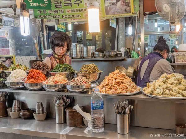 Auswahl an verschiedenen Streetfoodgerichten in einer Markthalle