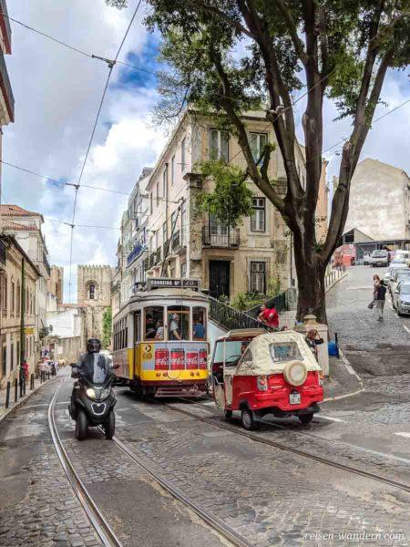 Alte gelbe Straßenbahn mit rotem Dreirad bei Kathedrale in Liss