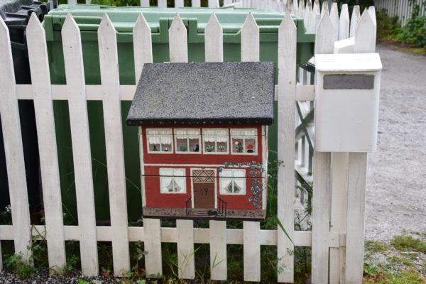 Ein detailliert bemalter Briefkasten hängt an einem weißen Zaun