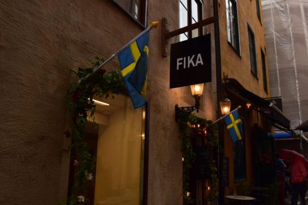 Ein Café trägt den Namen Fika. Daneben hängen 2 Schweden-Fahnen