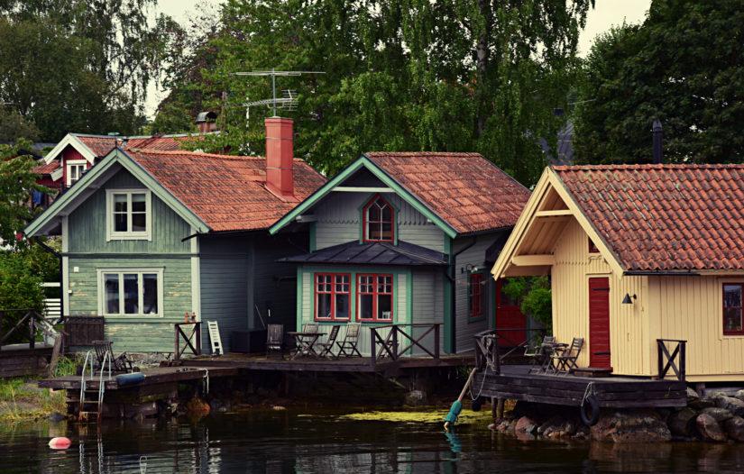 Direkt am Wasser stehen 3 Holzhütten im typisch schwedischem Stil und unterschiedlichen Farben.