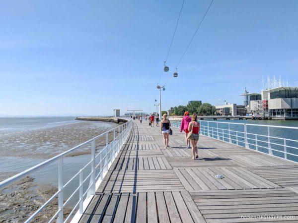 Fußgänger auf Uferpromenade mit Seilbahn in Lissabon