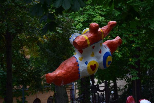 Eine abstrakte Skulptur in bunten Farben ist umgeben von Bäumen installiert