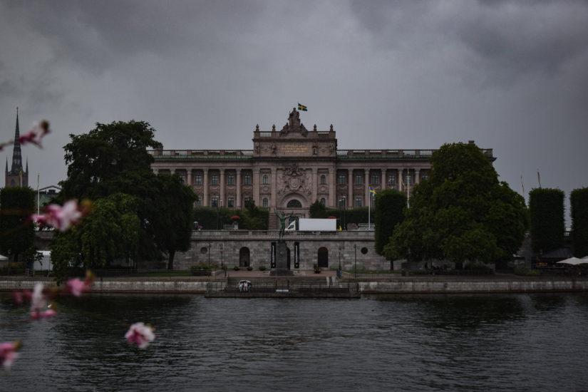 Unter Regenwolken steht das Parlament Stockholms direkt am Wasser