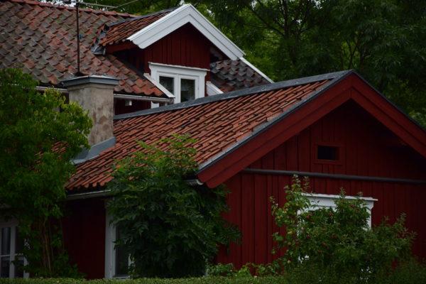 Das Dach einer roten Holzhütte ragt über die Baumwipfel