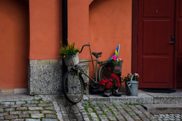 Vor einer orangenen Wand steht ein liebevoll verziertes Fahrrad